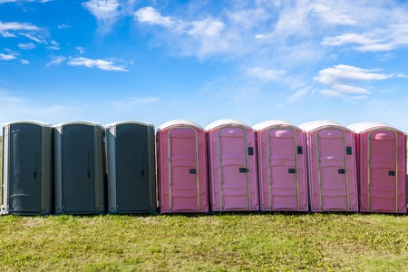 latrine: Gray and pink portable plastic toilets on an open field for an outdoor event