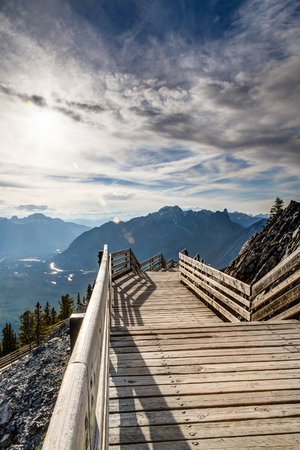 Interpretive walkway on the summit of Sulphur Mountain in Banff, Alberta, Canada, with sun peeking through the clouds and flare