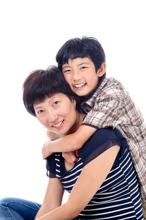 Asian boy hugs mom in affectionate pose  photo