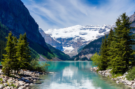 Beautiful Lake Louise with Victoria Glacier in the background and a glistening emerald lake  Several canoes can be seen at a distance on the lake