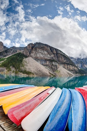 A fisheye view of Moraine Lake in the Canadian Rockies, with vibrant colored canoes on the foreground and the Valley of the Ten Peaks in the background. Vertical Orientation. Stock Photo