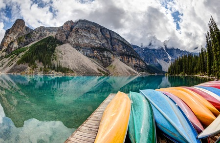 A fisheye view of Moraine Lake in the Canadian Rockies, with vibrant colored canoes on the foreground and the Valley of the Ten Peaks in the background.