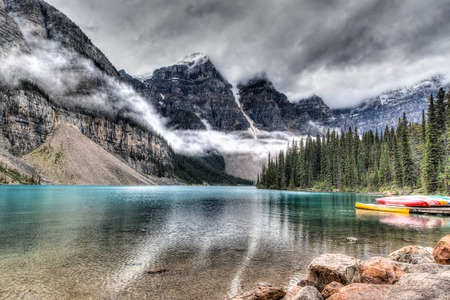 canadian rockies: Moraine Lake with clouds descending on the Valley of the Ten Peaks in the background and some canoes in the foreground.