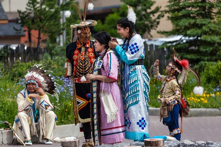 native american man: Young native Blackfoot Indian dancers put the finishing touches on their costumes for their performance during the Banff Summer Arts festival. The Banff Summer Arts Festival is the longest running arts festival in Canada held every summer since 1933. Editorial