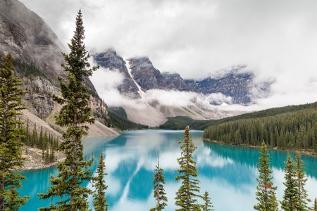 Fog and clouds descend onto the Valley of the Ten Peaks where glacier-fed Moraine Lake gives off its distinct turquoise blue color due to refraction of light off the rock flour at the bottom of the lake.