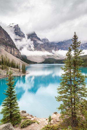 descend: Fog and clouds descend onto the Valley of the Ten Peaks where glacier-fed Moraine Lake gives off its distinct turquoise blue color due to refraction of light off the rock flour at the bottom of the lake.