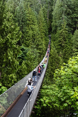 Visitors crossing the Capilano River on a suspension bridge in North Vancouver in British Columbia, Canada. The Capilano Suspension Bridge is 460 feet long and 230 metres above the river. Editorial