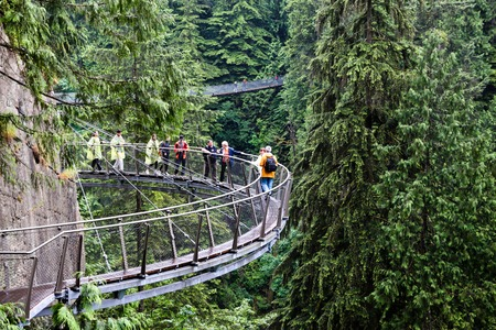 Visitors exploring the Capilano Cliff Walk through rainforest vegetation. It is a cantilevered and suspended walkways jutting out from the granite cliff face 230 metres above the Capilano River.