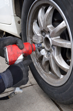 A pair of hands in work gloves holding an air impact wrench to change tires.