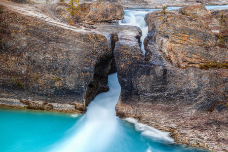 british columbia: Rushing waters at the Kicking Horse River carves a path through this ancient rock at Natural Bridge in Yoho National Park, British Columbia, Canada. Stock Photo