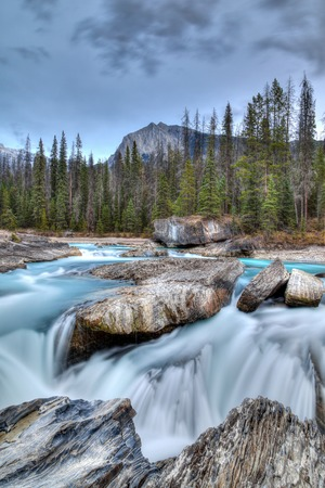 Rushing waters from the Kicking Horse River carves through the rocks at Natural Bridge in Yoho National Park in the Canadian Rockies. Vertical composition. photo