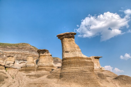 hoodoo: Hoodoos in Drumheller, Alberta. Hoodoos take millions of years to form and stand 5 to 7 metres tall. Each hoodoo is a sandstone pillar resting on a thick base of shale that is capped by a large stone.