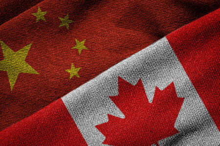 3D rendering of the flags of China and Canada on woven fabric texture. Concept of political, economic; cultural or social program partnership and cooperation between the two nations. China is Canada's second largest trading partner. Detailed textile patte