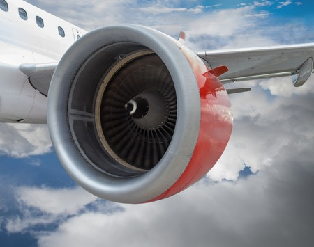 Commercial airplane with red engine in flight through clouds. Realistic engine spinning motion on close up. Archivio Fotografico
