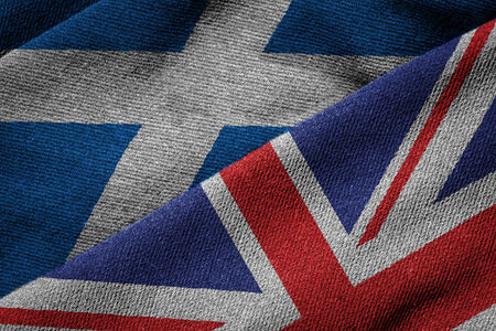 3D rendering of the flags of UK and Scotland on woven fabric texture. Concept of Scotland being part of the UK. Detailed textile pattern and grunge theme. Banque d'images