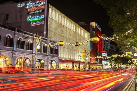 streaking: SINGAPORE - DECEMBER 12: Night view of famous festive Orchard Road in Singapore Dec. 12, 2014. Colorful street decorations and motion blur on streaking traffic tail lights during Christmas season.