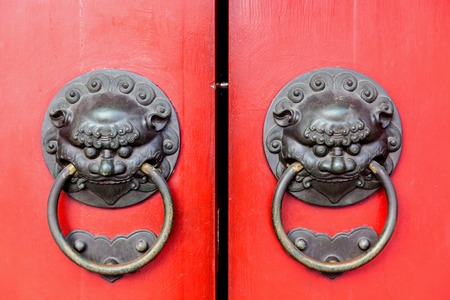 usher: Traditional Chinese doors with brass handles symbolic of lions heads. Its believe to ward off evil and usher in good luck for the occupants.