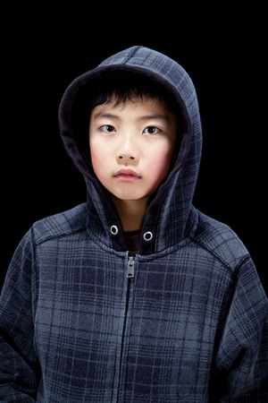 hooded shirt: Cute Asian boy wearing hooded sweatshirt posing in studio. Isolated on black.