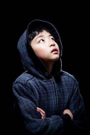 hooded sweatshirt: Cute Asian boy wearing hooded sweatshirt posing in studio. Isolated on black.