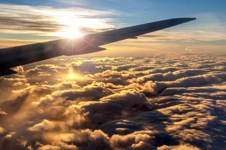 고의적 렌즈 황금 일출 외부 비행기 창보기는 효과를 비행기 날개의 실루엣을 통해 플레어. 비행기 아래 록키 산맥 위에 구름의 바다.