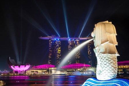 Merlion statue of Singapore watches over laser show emanating from Marina Bay Sands Hotel across the Marina Bay Harbor