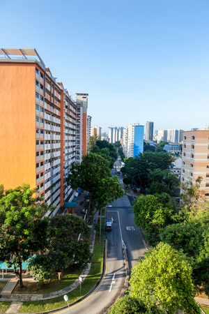 residential housing: A Singapore residential housing estate with apartment blocks surrounded by trees against a clear blue sky.