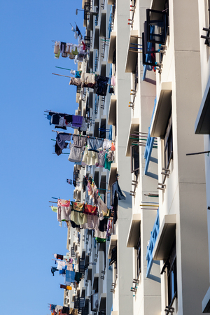 hdb: Typical Singapore public housing apartments where laundry is hung out to dry on bamboo poles from balconies.
