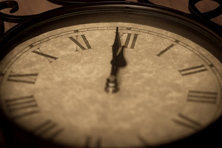 oclock: Antique clock showing minute to midnight with deliberate focus on the roman numeral 12 and shallow depth of field on the rest for effect. Stock Photo