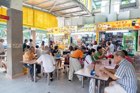싱가포르의 Whampoa Hawker Centre에서 인기있는 음식점에서 사람들이 먹습니다.
