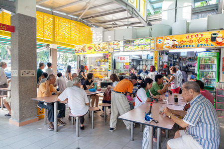 People eat at the popular food stalls in Whampoa Hawker Center in Singapore Éditoriale