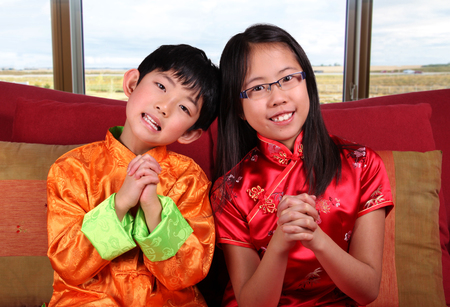 Two cute children in traditional Chinese New Year outfits making a Chinese-style greeting gesture.