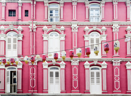 Pink Chinatown building facade in Singapore features elements of baroque and Victorian architecture designs built in the style of painted ladies. Editorial