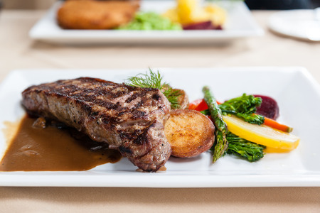 new york strip: Grilled juicy New York strip loin beef steak served with potatoes, fresh vegetables and marsala portobello mushroom sauce.