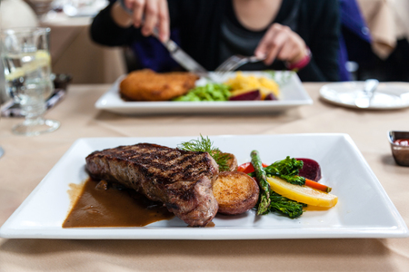 new york strip: A delicious strip loin beef steak meal served with fresh vegetables and marsala portobello mushroom sauce. Deliberate shallow depth of field on subject having a meal across the table.