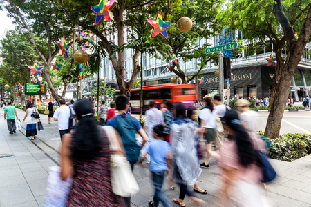 Shoppers and tourists walk along the pedestrian street of Orchard Road during Christmas season. The area is the prime shopping and entertainment district of Singapore.
