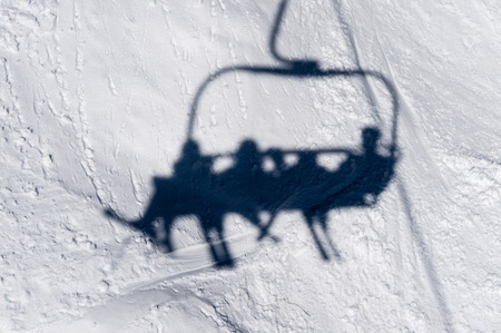 louise: Shadow of skiiers on lift chairs on the slopes of Lake Louise. Stock Photo