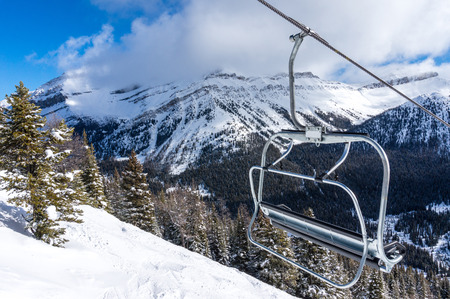 ski lift: Empty ski lift chair with Rocky Mountains in the background.