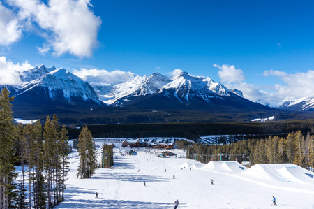 Skiers and snowboarders descend the slopes toward Lake Louise Lodge. Stock Photo
