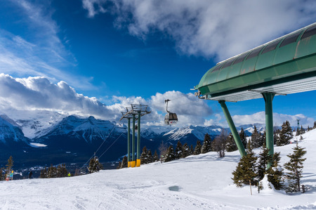 descend: Skiers descend the slopes at Lake Louise in Banff as gondolas ascend toward the disembarkment station. Lake Louise is a popular ski resort in Banff National Park, Canada.