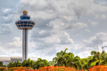 HDR rendering of Singapore Changi International Airport Traffic Controller Tower with cloudy skies in the background and beautiful trees and shrubs in the foreground. The airport tower is one of the most recognizable icons of Singapore.