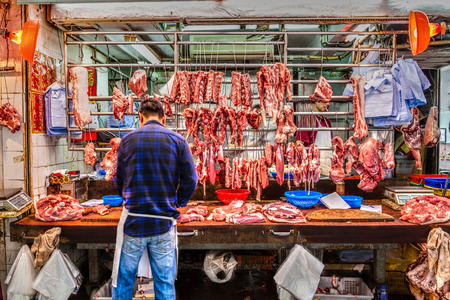 the cleaver: Butchers cut up pork for sale on Gage Street in the Central District of downtown Hong Kong. Stock Photo
