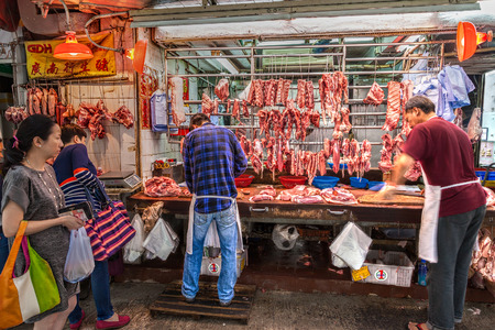 gage: Butchers cut up pork for sale on Gage Street in the Central District of downtown Hong Kong. Editorial