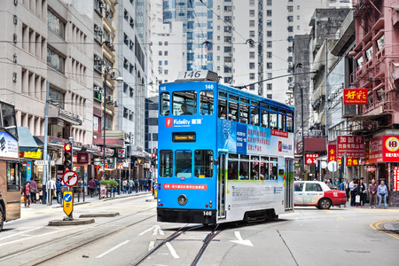 An electric tram bus turns into Des Voeux Road in the downtown Central District of Hong Kong. These historic streetcars have been in operation since 1904.
