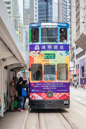 electric tram: Passengers board an electric tram on Des Voeux Road in the downtown Central District of Hong Kong. These historic streetcars have been in operation since 1904.