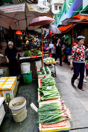 continuously: Shoppers patronize the fruit and vegetable stores along Graham Street in the Central District of downtown Hong Kong for the last time. The popular area was Hong Kongs oldest continuously operating street market for more than 160 years until Apr. 1 2015 w
