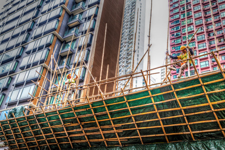 building industry: Two construction workers building a bamboo scaffolding on a construction site in Hong Kong. Bamboo scaffolding is popular in the Hong Kong building industry since the 1800s.