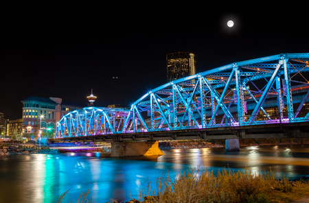 Full moon over Langevin Bridge at night in downtown Calgary. The truss bridge was built in 1910 and named after Sir HectorLouis Langevin one of the Fathers of the Canadian Confederation. It brings southbound traffic across the Bow River into the downtown  Banque d'images