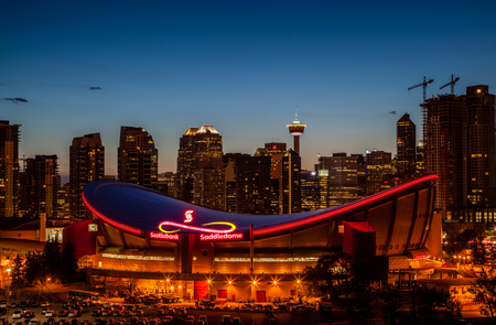 Calgary's skyline at dusk with the Scotiabank Saddledome in the foreground. The Saddledome with its unique saddle shape is home to the Calgary Flames NHL club and is one of the oldest professional hockey arenas in North America.