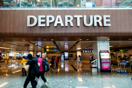disembarking: Travelers walk about Singapore Changi Airports departure hall. With three passenger terminals it is one of the largest transportation hubs in Asia with a total annual handling capacity of 66 million passengers.