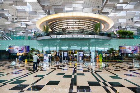 여행자는 싱가포르 창이 공항의 출발 홀에 대한 도보. 세 여객 터미널과 66 만명의 승객의 연간 총 처리 용량을 가진 아시아에서 가장 큰 교통 허브 중  에디토리얼
